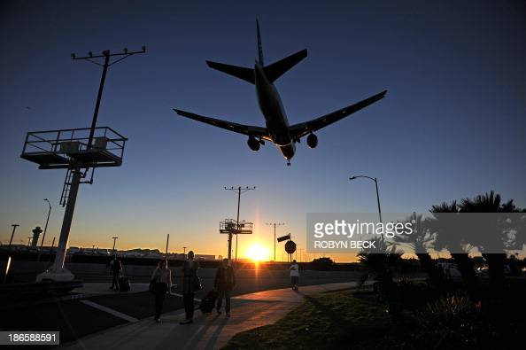 Passengers pull their luggage outside Los Angeles International Airport as a plane comes in for a landing at dusk November 1 2013 in Los Angeles...