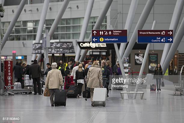 Passengers pull their luggage through a terminal building inside Duesseldorf airport operated by Flughafen Duesseldorf GmbH in Duesseldorf Germany on...