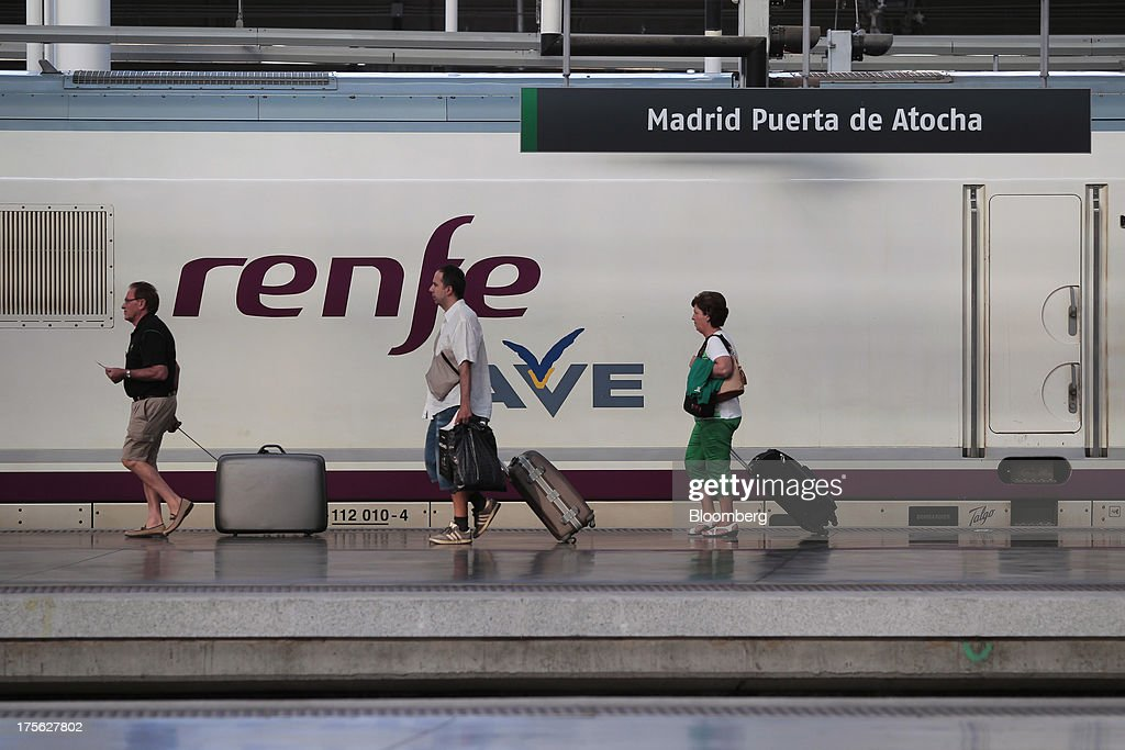 Passengers pull their suitcases along a platform beside an Alta Velocidad Espanola (AVE) high-speed train operated by Renfe Operadora SC at Atocha train station in Madrid, Spain, on Saturday, Aug. 3, 2013. Spain's state-owned rail operator Renfe plans to cut almost 500 jobs, or 4% of staff, as early as this year, ABC reports, citing comments by Public Works Minister Ana Pastor. Photographer: Antonio Heredia/Bloomberg via Getty Images