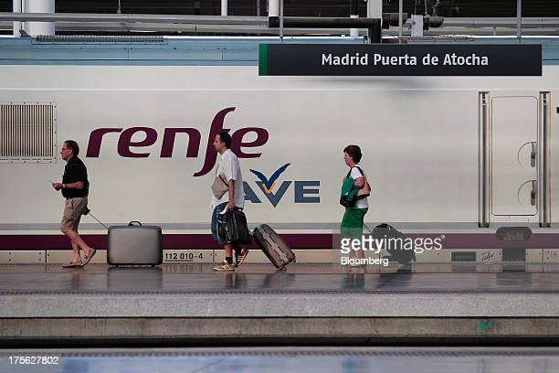 Passengers pull their suitcases along a platform beside an Alta Velocidad Espanola highspeed train operated by Renfe Operadora SC at Atocha train...