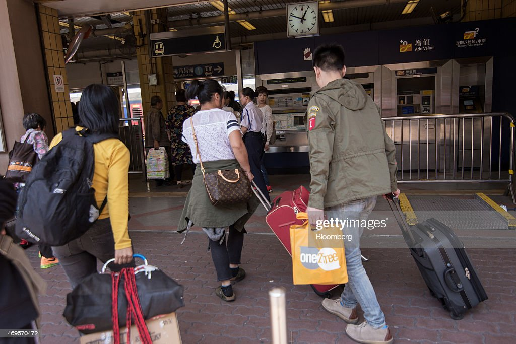 Passengers pulling luggage enter the MTR Corp's Sheung Shui train station in the Sheung Shui district near the border with mainland China in Hong...