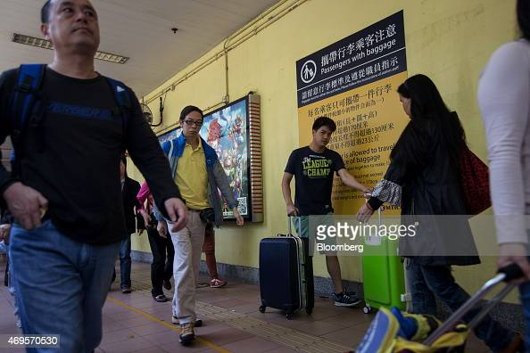 Passengers pushing luggage and shopping carts walk past a notice for baggage restrictions at the entrance to MTR Corp's Sheung Shui train station in...