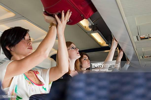 Los pasajeros putting equipaje en casilleros en avión