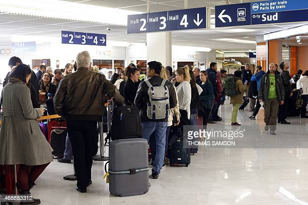 Passengers queue at a checkin desk on April 8 2015 at Orly airport outside Paris as hundreds of flights to and from France were expected to be...