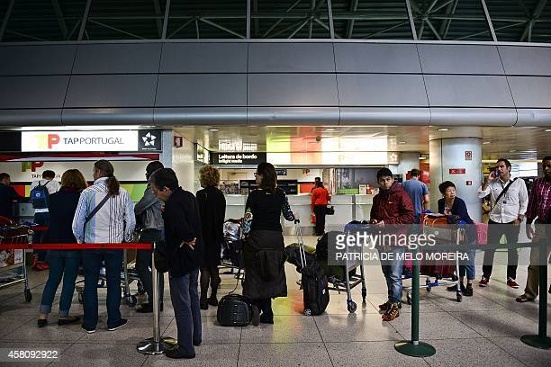 Passengers queue at a Portugese airline TAP customer service desk at Lisbon's airport during a strike on October 30 2014 Air traffic was disrupted...