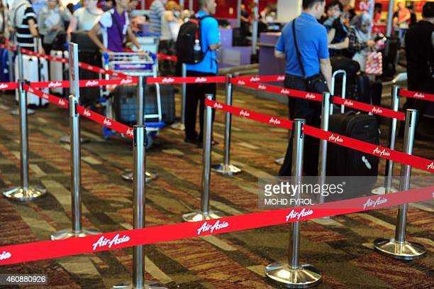 Passengers queue at an AirAsia checkin counter inside terminal 1 at Changi international airport in Singapore on December 29 2014 Shares in AirAsia...