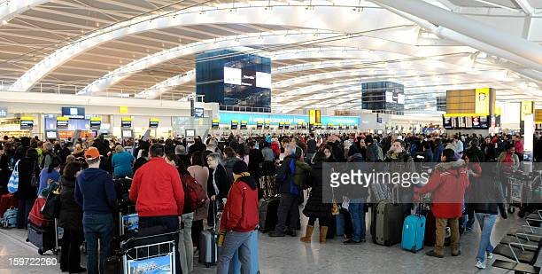 Passengers queue at for the checkin desks at a busy Heathrow airport in west London on January 19 2013 after hundreds of flights were cancelled due...