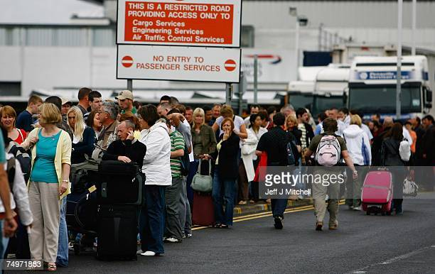 Passengers queue at Glasgow Airport after an incident with a car being driven at the airport's main terminal July 1 2007 in Glasgow Scotland...