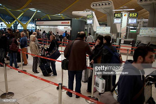 Passengers queue at Iberia's customer care office before a protest of Spanish Airline Iberia staff against job cuts at Barajas Airport on February 18...