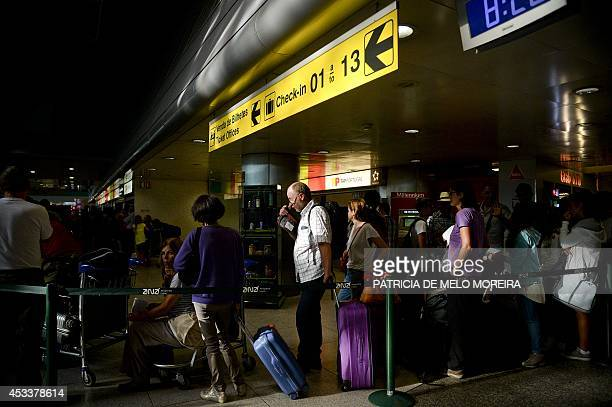 Passengers queue at TAP's customer service desk at Lisbon's Airport during a strike on August 9 2014 Pilots at Portuguese stateowned airline TAP...