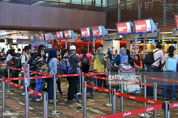 Passengers queue at the AirAsia checkin counter before departure at Singapore Changi airport terminal on December 28 2014 Rescuers scoured the sea...