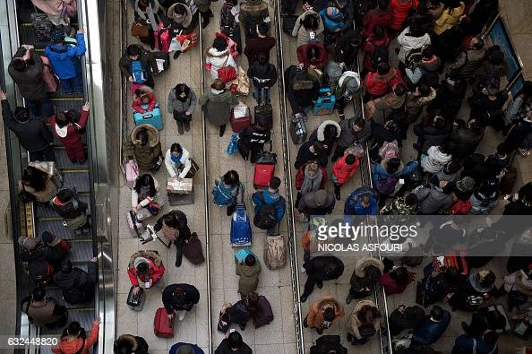TOPSHOT Passengers queue at the train station as they prepare to travel to their hometowns for the 'Spring Festival' or Lunar New Year on January 23...