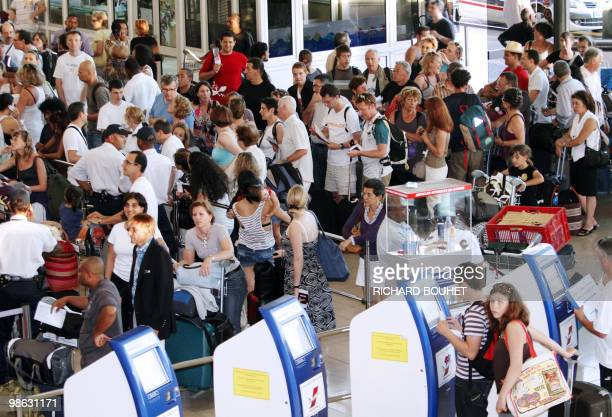 Passengers queue before checking in at Gillot airport in the French Indian ocean island of Saint Denis de la Reunion on April 22 2010 Two thousand...