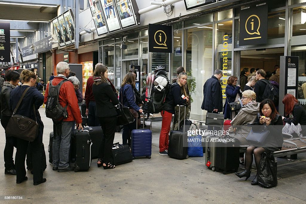 Passengers queue for the information desk in the Gare Montparnasse rail station in Paris, on May 31, 2016, at the start of a strike by employees of French state-owned rail operator SNCF to protest against government labour reforms. France is bracing for a week of severe disruption to transport after unions called for more action in their bitter standoff with the Socialist government over its labour market reforms. / AFP / MATTHIEU