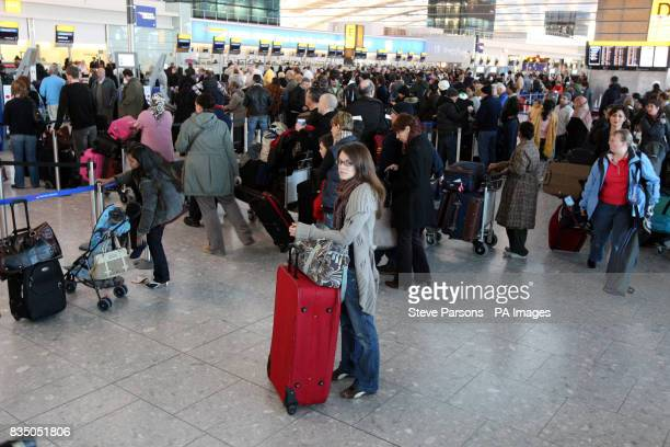 Passengers queue in Terminal 5 at Heathrow Airport after nearly 800 flights were cancelled at the airport yesterday due to heavy snowfall and others...