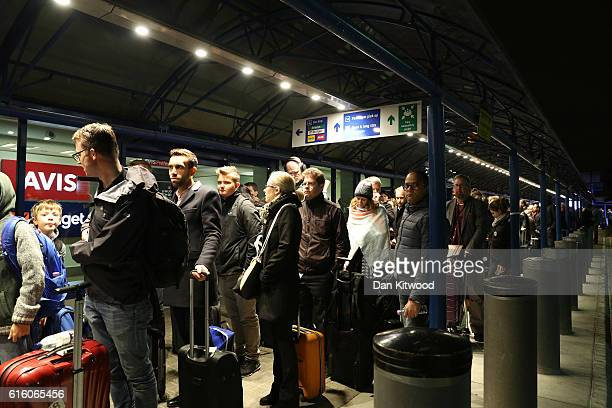 Passengers queue outside the terminal after it was evacuated at London City Airport following a chemical incident on October 21 2016 in London...