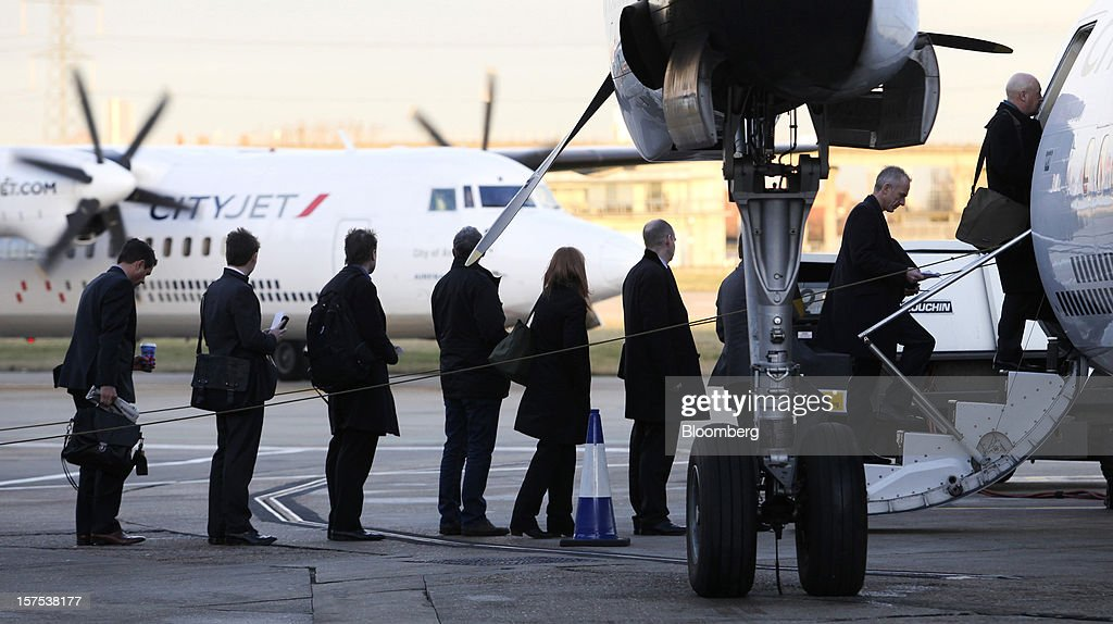 Passengers queue to board a Fokker 50 aircraft, operated by CityJet Ltd., at City Airport in London, U.K., on Tuesday, Dec. 4, 2012. Air France-KLM Group's CityJet unit is studying options for a new investor, with a trade buyer a possibility given its strength at London City airport, Chief Executive Officer Christine Ourmieres said in an interview. Photographer: Chris Ratcliffe/Bloomberg via Getty Images