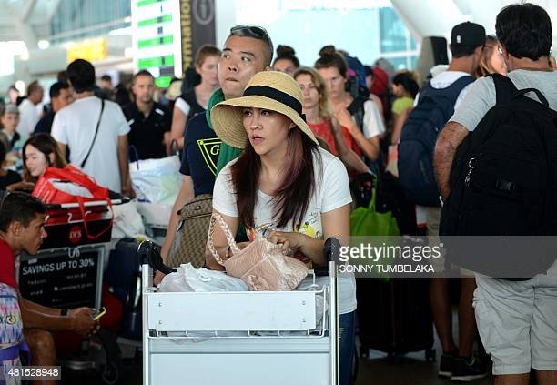 Passengers queue to get information about delayed flights at the international departure area of Bali's Ngurah Airport in Denpasar on July 22 2015...