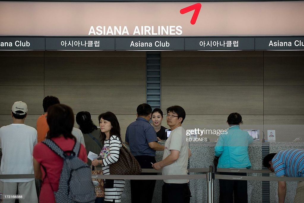 Passengers queue up at an Asiana Airlines desk at Incheon international airport in Seoul on July 9, 2013. Investigators probing the Asiana Airlines plane crash in San Francisco began interviewing cockpit crew of the Boeing 777 amid mounting indications that pilot error may have caused the fatal accident. AFP PHOTO / Ed Jones