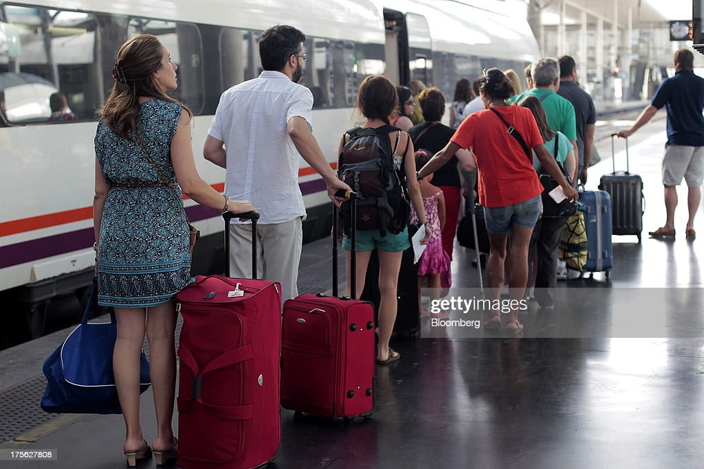 Passengers queue with their luggage as they board a train operated by Renfe Operadora SC as it sits at a platform at Atocha train station in Madrid, Spain, on Saturday, Aug. 3, 2013. Spain's state-owned rail operator Renfe plans to cut almost 500 jobs, or 4% of staff, as early as this year, ABC reports, citing comments by Public Works Minister Ana Pastor. Photographer: Antonio Heredia/Bloomberg via Getty Images