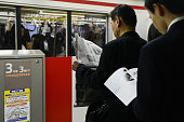 Passengers read a newspaper and a magazine while waiting on the platform for the next train on the Marunouchi subway line operated by Tokyo Metro Co...