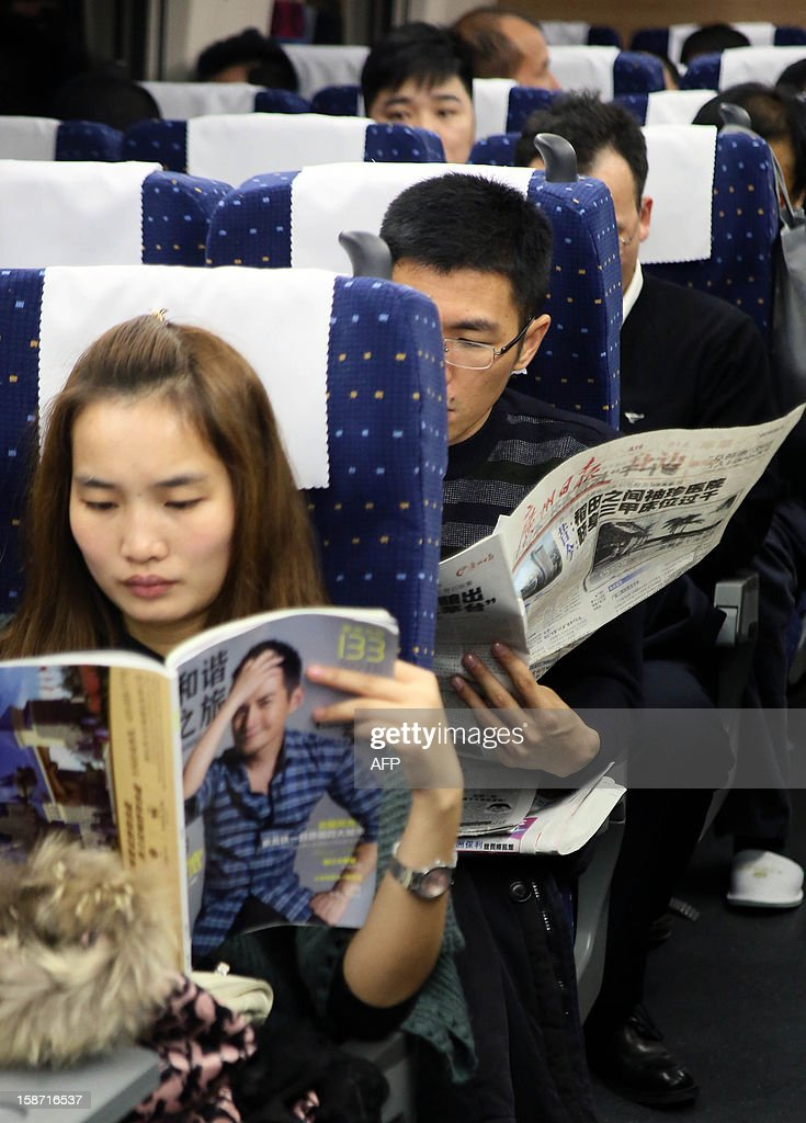 Passengers read newspapers on the new 2,298-kilometre (1,425-mile) line between Beijing and Guangzhou in Guangzhou, south China's Guangdong province on December 26, 2012. China started service on December 26 on the world's longest high-speed rail route, the latest milestone in the country's rapid and -- sometimes troubled -- super fast rail network. The opening of this new line means passengers will be whisked from the capital to the southern commercial hub in just eight hours, compared with the 22 hours previously required. CHINA