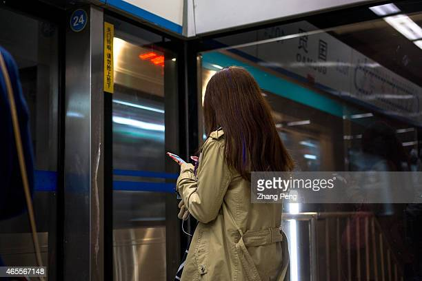 Passengers read their smart phones while waiting for the subway train People who have the smartphoneaddict nowadays are called Smartphone zombies