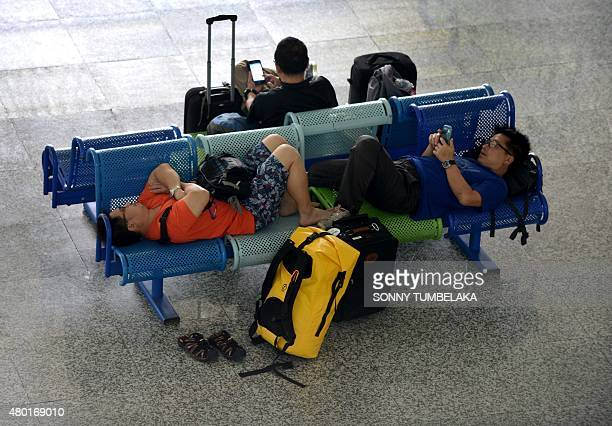 Passengers rest in the international terminal at Bali's Ngurah Rai airport in Denpasar waiting for information of flight delays due to volcanic ash...