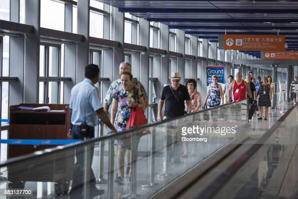 Passengers ride a moving walkway to board the Ovation of the Seas Quantumclass cruise ship operated by Royal Caribbean Cruises Ltd at the Kai Tak...