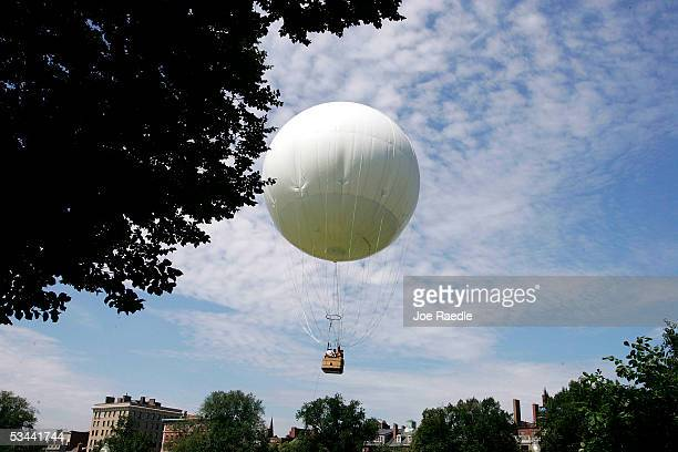 Passengers ride in the gondola of the AeroBalloon USA's giant helium balloon floating above the grounds of the Boston Commons August 19 2005 in...