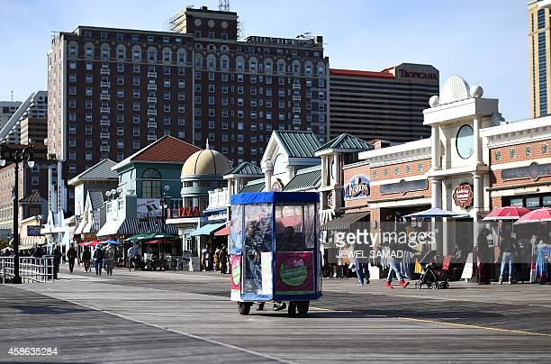Passengers ride on a 'push cab' along the boardwalk in Atlantic City New Jersey on November 8 2014 For decades Atlantic City was a popular vacation...