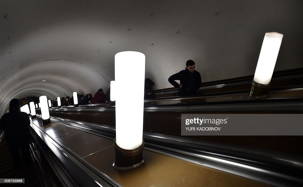 Passengers ride on an escalator at Kuznetsky Most metro station in Moscow, on February 12, 2016. AFP PHOTO / YURI KADOBNOV / AFP / YURI KADOBNOV