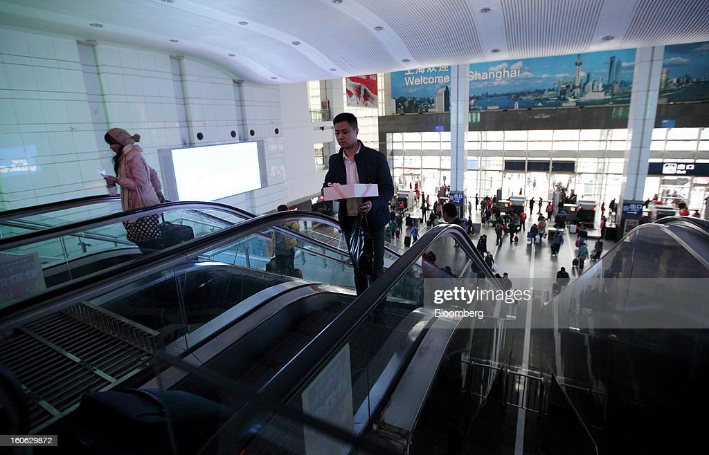 Passengers ride on escalators inside Shanghai Railway Station in Shanghai, China, on Sunday, Feb. 3, 2013. Forecasts of snow and rain across China threaten to disrupt the travel plans of millions of Chinese heading home for the Lunar New Year holidays that start Feb. 9, the national weather agency warned. Photographer: Tomohiro Ohsumi/Bloomberg via Getty Images