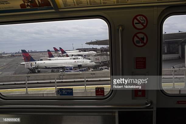 Passengers riding the AirTrain pass by the Delta Air Lines terminal at the John F Kennedy International Airport February 26 2013 in the Queens...