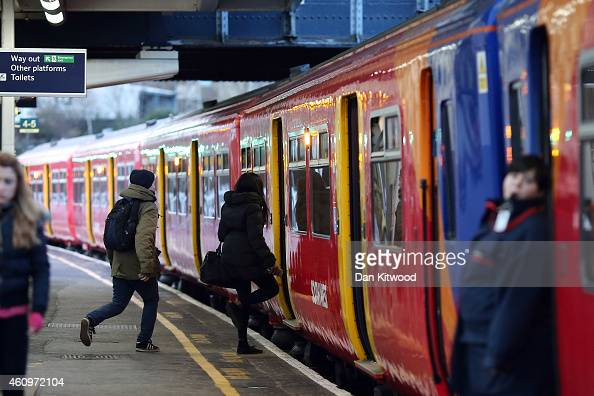 Passengers run to board a train at Clapham Junction on January 2 2015 in London England Increased rail fares averaging 25% come into effect today...