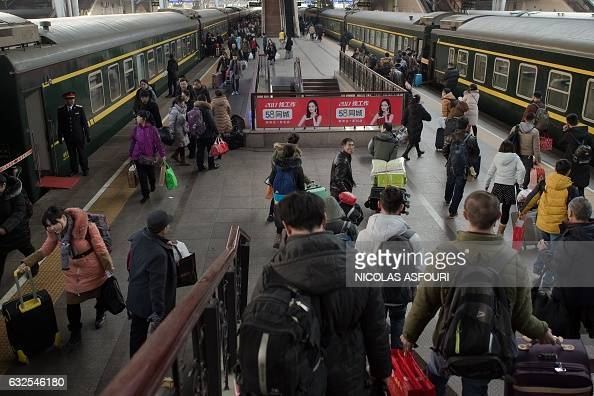 Passengers rush to the platform to board their trains to travel to their hometowns for the 'Spring Festival' or Lunar New Year on January 24 2017 at...