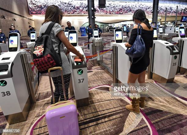 Passengers scan their passports at automated immigration gates at the newlyopened Changi International Airport's Terminal 4 in Singapore on October...