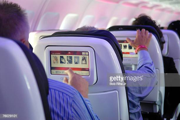 Passengers seated in customdesigned leather chairs try out Virgin America airlines inflight entertainment system which includes ondemand movies...