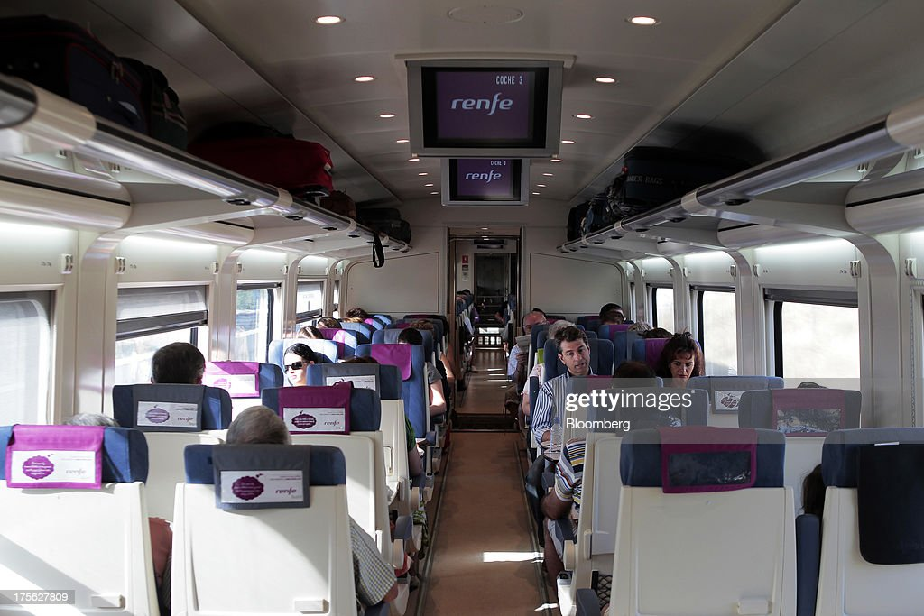 Passengers sit aboard a train operated by Renfe Operadora SC as it travels from Madrid to Valencia in Spain, on Saturday, Aug. 3, 2013. Spain's state-owned rail operator Renfe plans to cut almost 500 jobs, or 4% of staff, as early as this year, ABC reports, citing comments by Public Works Minister Ana Pastor. Photographer: Antonio Heredia/Bloomberg via Getty Images