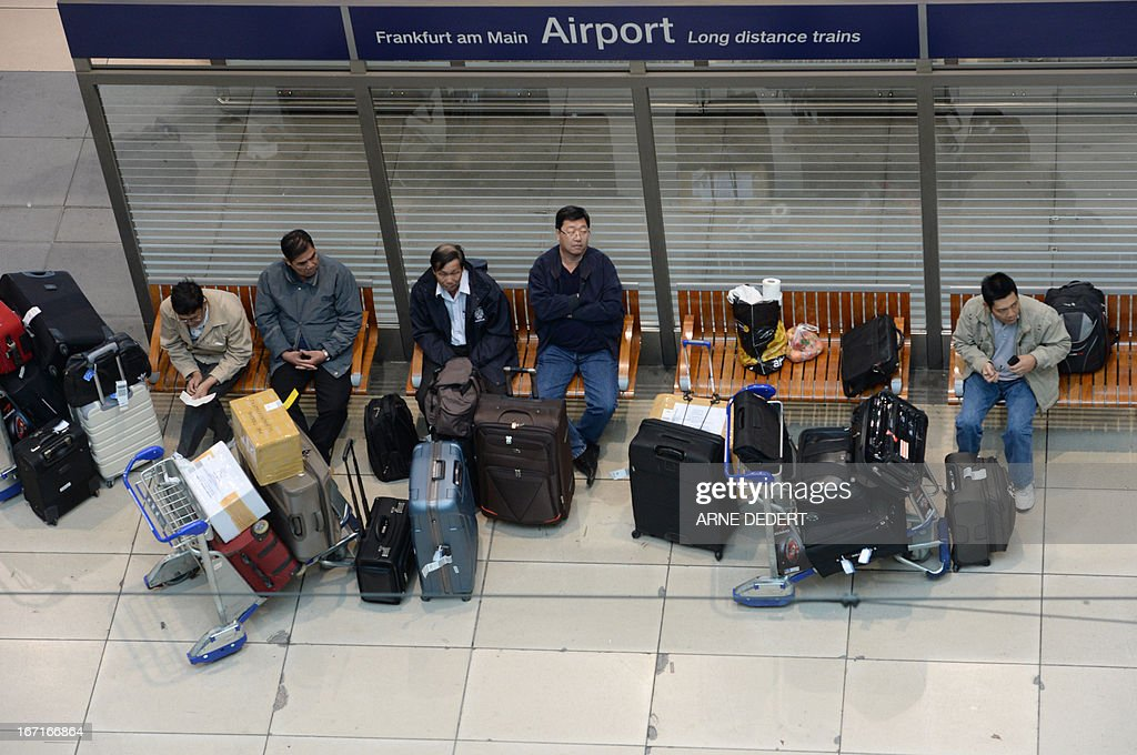 Passengers sit at the stations for long distance trains during a warning strike of ground staff of German airline Lufthansa at the airport in Frankfurt am Main, western Germany, on April 22, 2013. German airline Lufthansa said it has cancelled most of its domestic, European and long-haul flights at six German airports due to strike action by ground personnel and some cabin crew.
