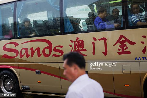 Passengers sit in a shuttle bus for Sands Macau hotel operated by Sands China Ltd a unit of Las Vegas Sands Corp in Macau China on Saturday Aug 29...