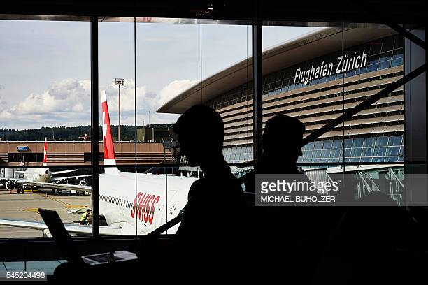 Passengers sit in front of an aircraft of Swiss International Airlines on July 6 2016 at the Zurich Airport in Zurich / AFP / MICHAEL BUHOLZER