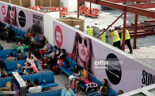 Passengers sit in the departures lounge as construction work progresses behind temporary hoardings at Stansted Airport operated by Manchester...