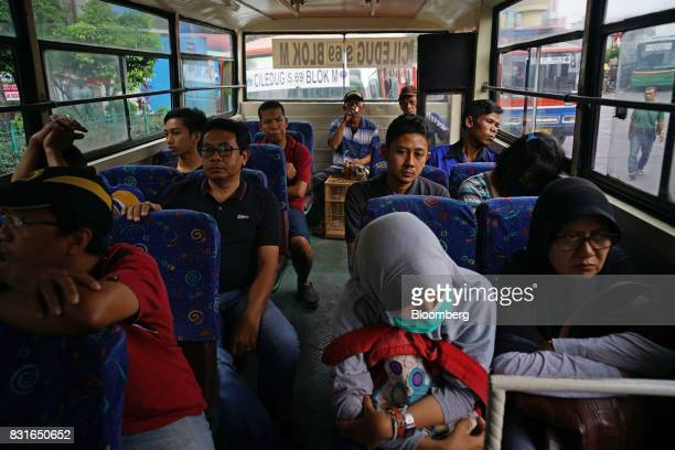 Passengers sit inside a bus at the Blok M bus terminal in Jakarta Indonesia on Sunday Aug 13 2017 President Joko Widodo is seeking hundreds of...