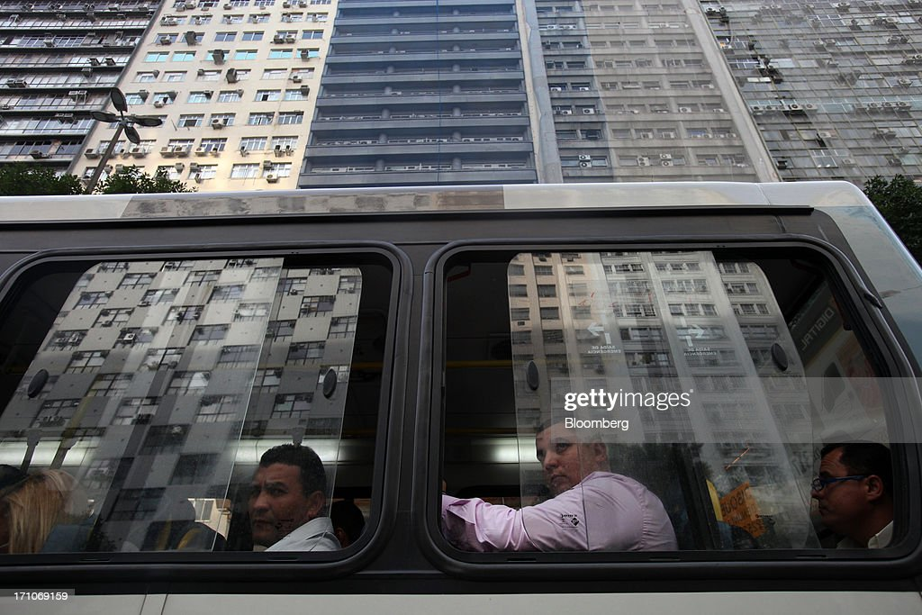 Passengers sit on a bus driving along Presidente Getulio Vargas Avenue in Rio de Janeiro, Brazil, on Friday, June 21, 2013. Brazils swelling street rebellion claimed its second fatality in the largest and most violent protests yet, as 1 million demonstrators rallied for better public services and an end to corruption. Photographer: Dado Galdieri/Bloomberg via Getty Images