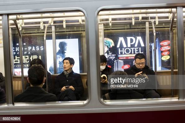 Passengers sit on a train in front of advertising for the APA hotel group at a subway station in Tokyo on February 1 2017 Japanese organisers of this...