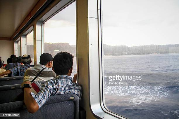 Passengers sit on an inside deck onboard a ferry transporting passengers and transportation car and motorcycle sailing in the middle of Bali sea on...