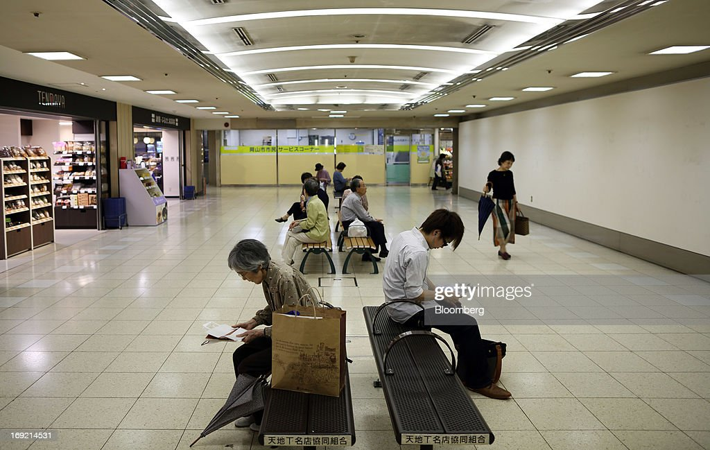 Passengers sit on benches at a bus terminal in Okayama, Japan, on Tuesday, May 21, 2013. The Bank of Japan, forecast to maintain plans for expanded monetary easing at a meeting ending on May 22, is targeting 2 percent inflation in two years after more than 10 years of entrenched deflation. Photographer: Tomohiro Ohsumi/Bloomberg via Getty Images