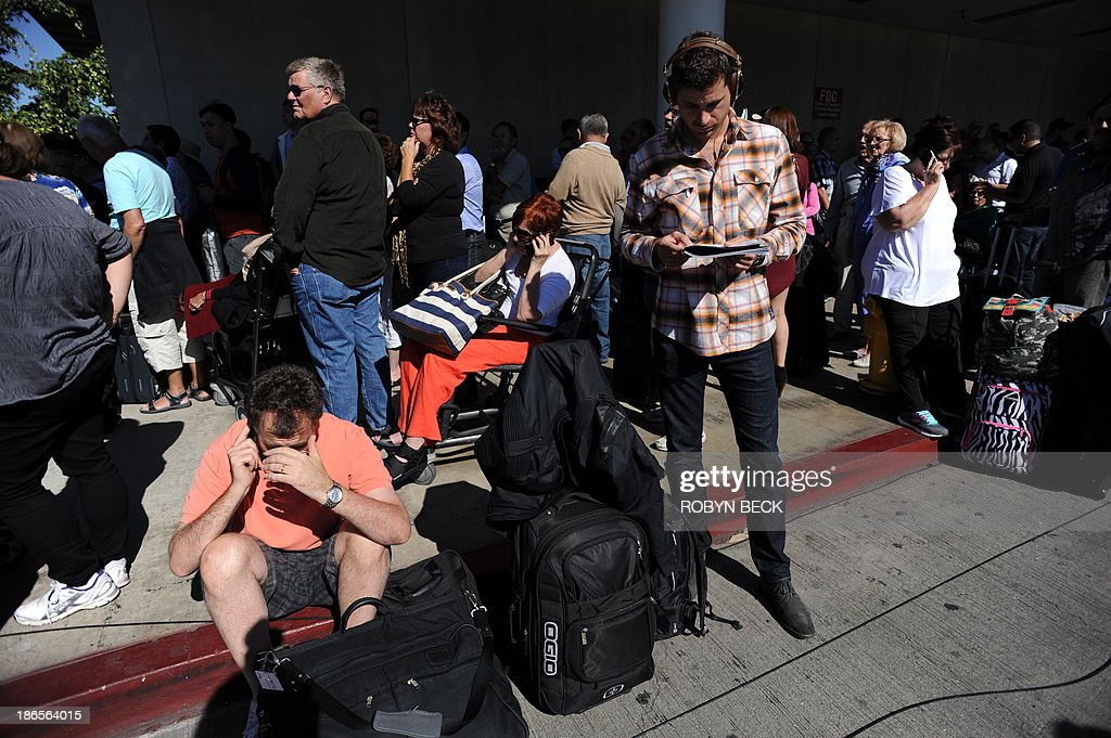 Passengers sit on the curb at Los Angeles International Airport on November 1, 2013 after a gunman reportedly opened fire at a security checkpoint. Police believe a gunman who opened fire at Los Angeles airport Friday acted alone, a police chief said, while not confirming reports that the shooter and one victim were killed. 'We believe at this point that there was a lone shooter, that he acted,' said Patrick Gannon, head of the LAX police force, saying he 'was the only person who was armed in this incident.' Seven people were injured, including six taken to hospital, said the head of the LA Fire Department James Featherstone, briefing reporters for the first time a couple of hours after the incident.