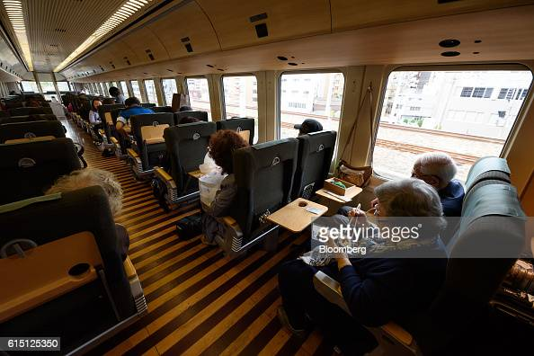 Passengers sit onboard the Yufuin No Mori limited express service train operated by Kyushu Railway Co as it travels from Hakata to Yufuin in Fukuoka...